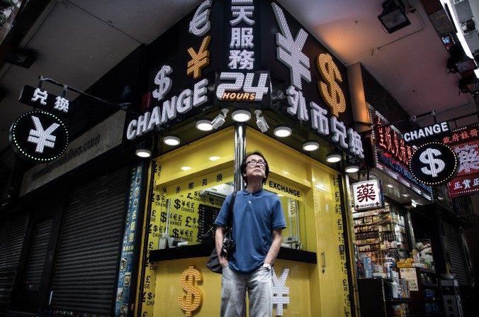 Un hombre frente a una casa de cambio de Hong Kong. (Philippe Lopez/AFP/Getty Images)