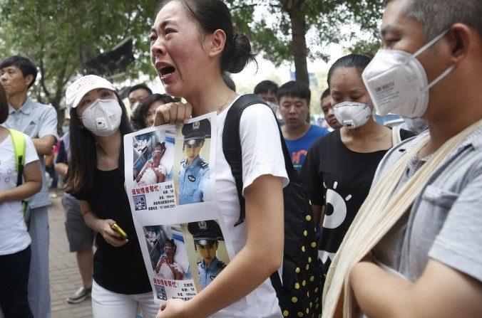 Familiares de bomberos desaparecidos protestan frente a un hotel de Tianjin donde se realizó una conferencia de prensa. (STR/AFP/Getty Images)