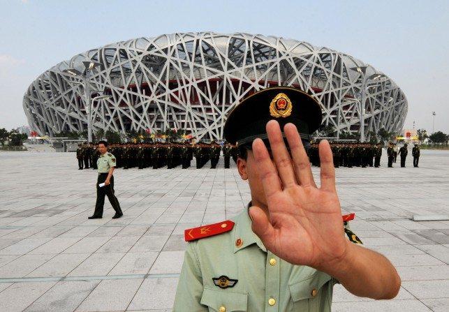 Un policía chino trata de impedir la toma de fotografías del ensayo de un desfile militar frente al Estadio Olímpico de Beijing el 21 de julio de 2008. (Mark Ralston/AFP/Getty Images)