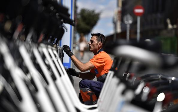Empleado municipal lleva a cabo el mantenimiento y las reparaciones preventivas en una estación de bicicletas eléctricas públicas cuota BiciMad en Madrid el 13 de agosto de 2015. Mientras que otras ciudades europeas como Londres y París establecieron esquemas de bicicletas compartidas antes, Madrid es la primera ciudad importante para ofrecer un sistema que sólo utiliza bicicletas eléctricas, lanzado en junio de 2004. Photo credit should read GERARD JULIEN/AFP/Getty Images)