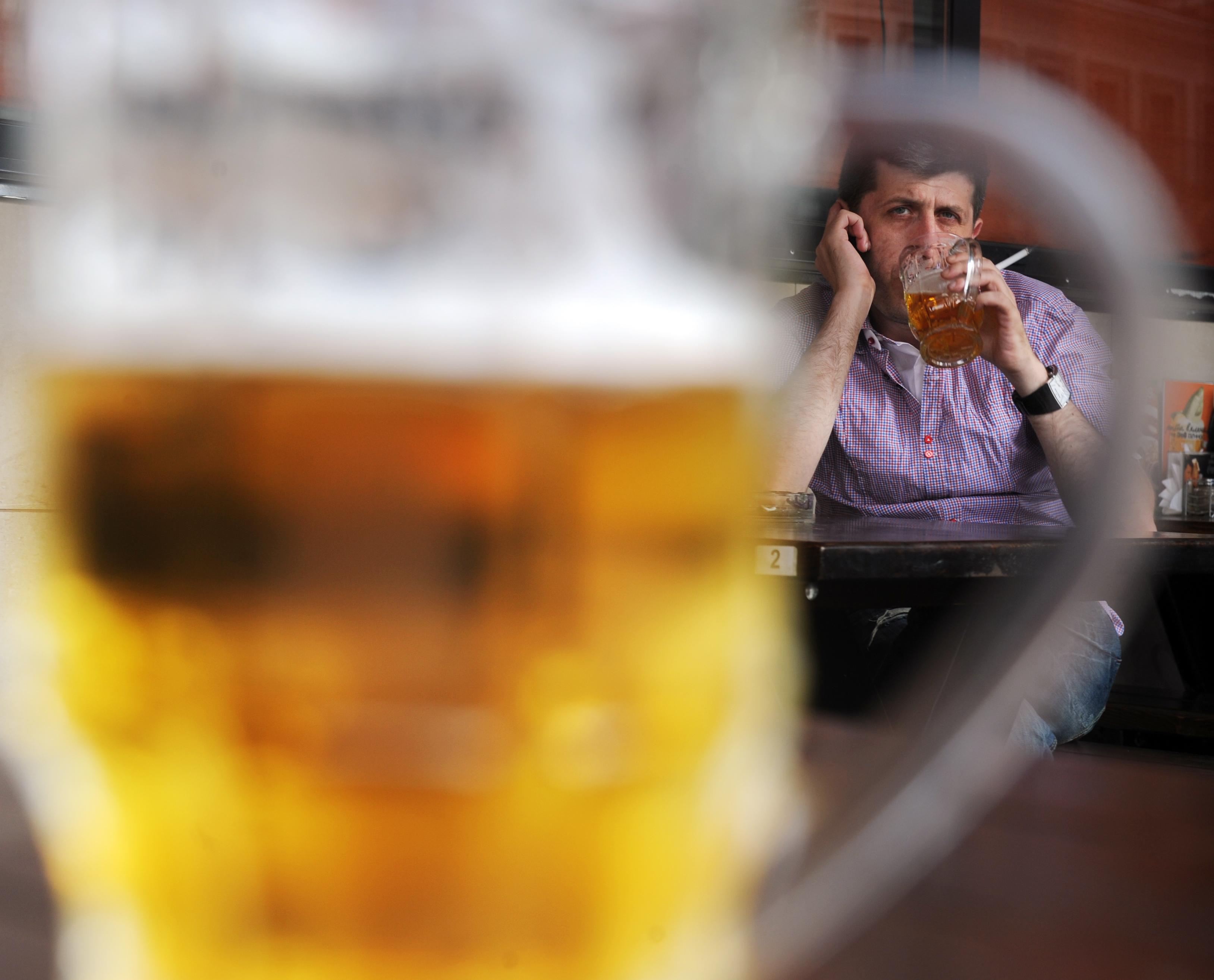Una imagen tomada el 26 de agosto de 2011 muestra a un hombre sentado detrás de un vaso de cerveza en un bar al aire libre de Moscú? S. Con un plumazo presidencial, la cerveza fue reclasificada recientemente como una bebida alcohólica en Rusia, ya no un alimento, y sus ventas han de limitarse a reducir el abuso del alcohol. Pero a partir de enero 2013 una nueva ley de licencia firmada por el presidente Dmitry Medvedev, prohibirá la venta de cerveza 11 p.m.-08 a.m. excepto en bares y cafeterías (Photo credit should read DMITRI KOSTYUKOV / AFP / Getty Images)