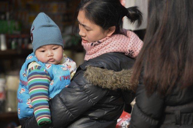 Una madre cargando a su bebé en las calles de Shanghái. (Peter Parks/AFP/Getty Images)
