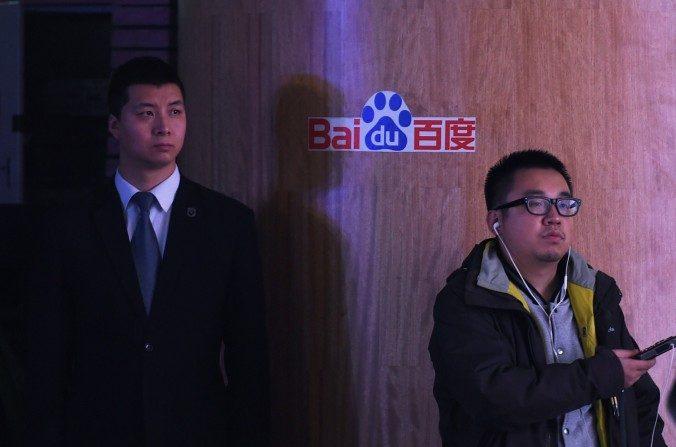 Un periodista y un guardia de seguridad permanecen cerca de un logo de Baidu durante una conferencia de prensa en la sede de Baidu en Beijing el 17 de diciembredel 2014. (Greg Baker / AFP / Getty Images)