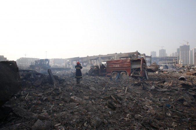 Un bombero se ve grabando las secuelas en el lugar de las explosiones en Tianjin el 15 de agosto de 2015. (STR / AFP / Getty Images)