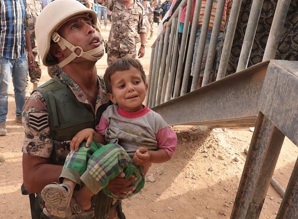 Un soldado jordano lleva a un joven refugiado sirio en el campamento improvisado al-Roqban, en la frontera con Siria, antes de conducir a un grupo de refugiados a la ciudad oriental de Ruwaished donde serán recibidos y verificados por las autoridades jordanas el 10 de septiembre de 2015. (KHALIL MAZRAAWI/AFP/Getty Images)