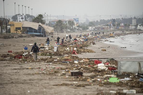 Residentes locales camina en medio de los escombros dejados en la playa por el tsunami que se produjo un terremoto de 8,3, en Coquimbo, al norte de Santiago, el 18 de septiembre de 2015. Desde entonces se han producido más de 500 réplicas. (MARTIN BERNETTI/AFP/Getty Images)