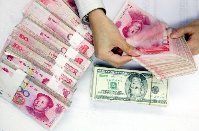 Un empleado cuenta montones de yuanes y dólares en un banco de Shanghai, China. (China Photos / Getty Images)