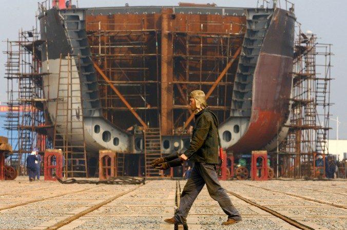Un trabajador camina en el casco gigante de un barco que se está construyendo en un muelle de unaempresa estatal en Chongqing, el 12 de febrero de 2009. (China Photos / Getty Images)