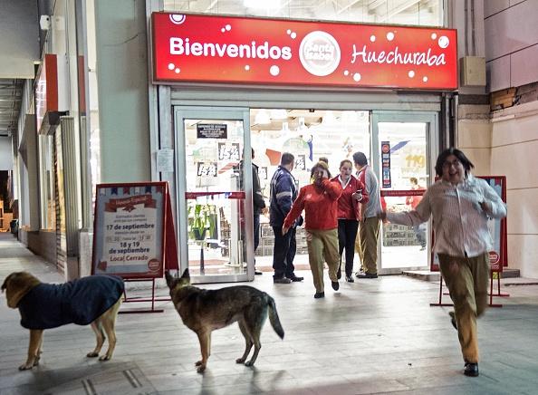 La gente deja un supermercado durante un fuerte sismo en Santiago el 16 de septiembre de 2015. Un fuerte terremoto de 7,2 grados de magnitud sacudió el centro de Chile el miércoles, dijeron sismólogos locales, lo que provocó una alerta de tsunami, lo que desató el pánico y sacudiendo edificios (Photo credit should read MARTIN BERNETTI / AFP / Getty Images)
