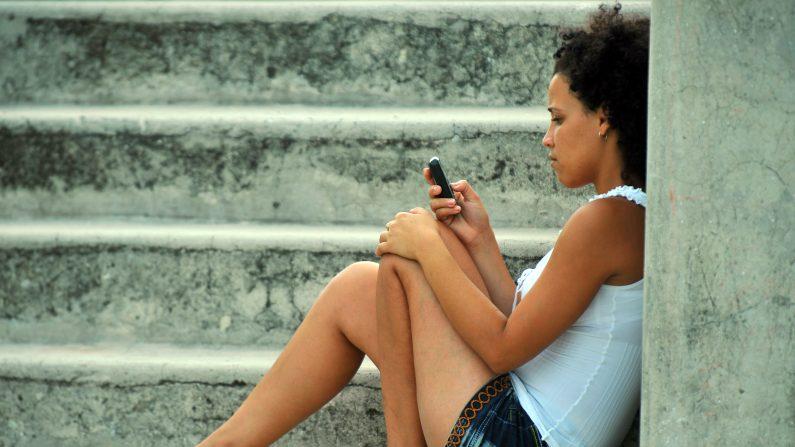 Una mujer joven cubano usa su teléfono móvil en La Habana . ( Photo credit should read STR / AFP / Getty Images )