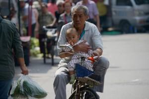 Un hombre mayor circula en bicicleta cargando un bebé con un brazo por una calle en Beijing el 8 de septiembre de 2015. (Wang Zhao/AFP/Getty Images)
