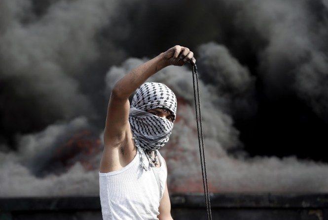 Un manifestante palestino se prepara para lanzar una piedra con una honda durante los enfrentamientos con las fuerzas de seguridad israelíes en la ciudad cisjordana de Al-Bireh, en la periferia norte de Ramallah, el 20 de octubre de 2015. (THOMAS COEX/AFP/Getty Images)
