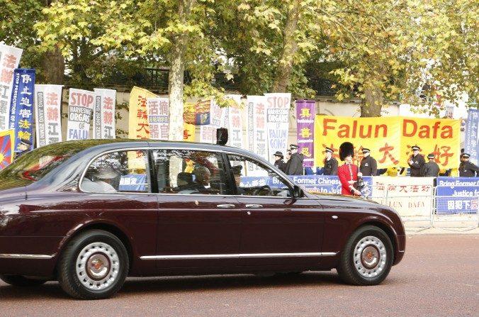 La Reina de Inglaterra sale del Palacio de Buckingham y pasa frente a los manifestantes que protestaban ante la visita de Xi Jinping, entre ellos, practicantes de Falun Gong, Amnistía Internacional y Free Tibet. (Simon Gross/La Gran Época)