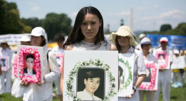 Una mujer sostiene la foto de un hombre torturado a muerte en China por practicar Falun Gong, en un acto conmemorativo en Washington DC, julio de 2014. (Edward Dai/La Gran Época)