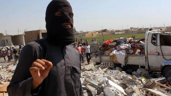 Captura de video donde se ve a un yihadista del ISIS frente a los escombros de una casa presuntamente derrumbada luego de que ISIS derribara un avión sirio, septiembre de 2014. (AFP/Getty Images)