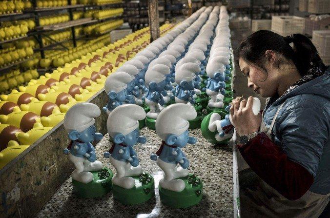 Trabajadores chinos pintan autorizados 'Pitufos' de cerámica sin terminar en la fábrica Shunmei Group (SMG) durante una visita el7 de diciembrede 2014 en Dehua, China. (Kevin Frayer / Getty Image)