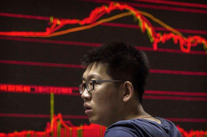 Un corredor de bolsa chino observa los cambios de las acciones en una casa local de bolsa el 27 de agosto de 2015 en Beijing, China. (Kevin Frayer/Getty Images)