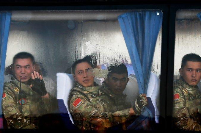 Las Tropas del Ejército Popular de Liberación chino miran desde un autobús cuando llegan a la puerta de Tiananmen en Beijing el3 de septiembre. El régimen chino planea reestructurar sus fuerzas armadas, y el control de sus unidades de piratas informáticos podrían ser desplazadas. (Andy Wong / Getty Images)