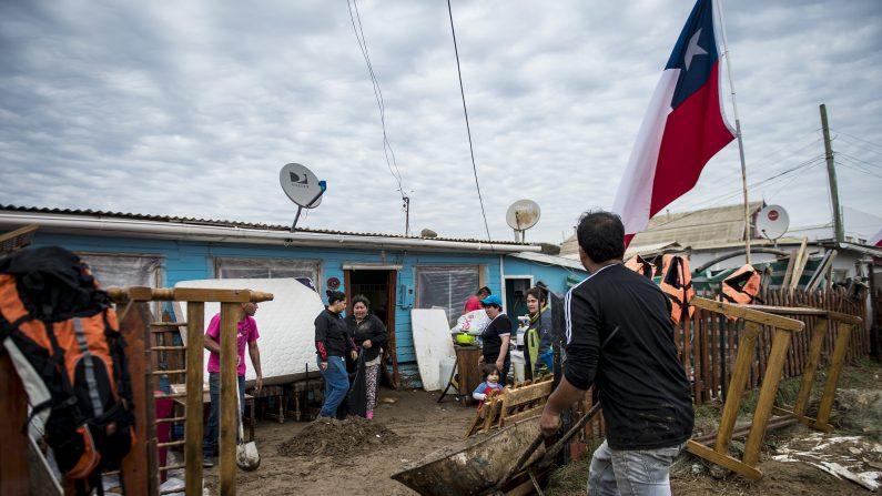 Los residentes locales limpian su hogar de los escombros dejados por el tsunami que se produjo un terremoto de 8,3 que dejó 12 muertos y cinco desaparecidos más , en Coquimbo , a 450 km al norte de Santiago , el 18 de septiembre de 2015. AFP PHOTO MARTIN BERNETTI ( Photo credit should leer MARTIN BERNETTI / AFP / Getty Images )