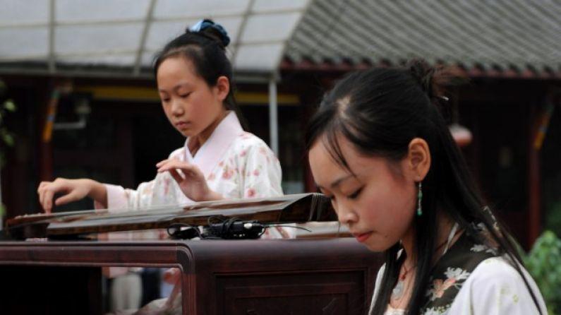 Jóvenes chinas tocan el clásico y complicado instrumento guqin, pariente de la cítara. (China Photos / Getty Images)