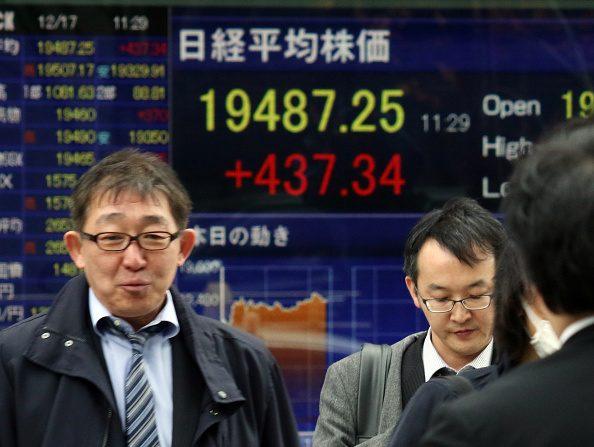 Los peatones junto a una tabla de precios de parte que muestra los primeros números en la bolsa de valores de Tokio (crédito de foto debe leer YOSHIKAZU TSUNO/AFP/Getty Images)