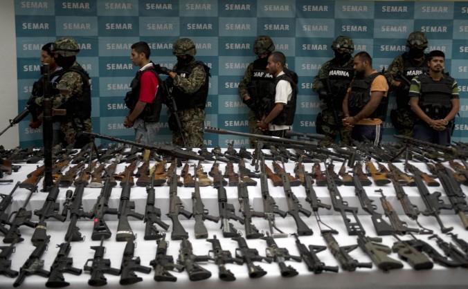 Marinos mexicanos acompañan a cinco supuestos traficantes de drogas del cartel de droga Zetas, frente a granadas, armas de fuego, cocaína y uniformes militares en la Ciudad de México, 9 de junio de 2011. (YURI CORTEZ/AFP/Getty Images)