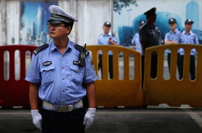 Policías chinos hacen guardia fuera del Tribunal Popular Intermedio de Jinan, el25 de agostodel 2013, en Jinan, China. (Feng Li / Getty Images)
