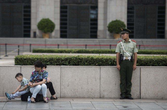 Un guardia paramilitar chino observa a una familia en la Plaza Tiananmen el01 de septiembredel 2015. (Fred Dufour / AFP / Getty Images)