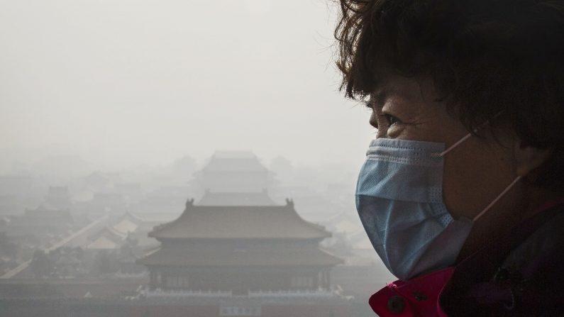 Una mujer China lleva una máscara debido a la densa neblina de humo causada por el aire contaminado en Beijing, Este lunes 7 de diciembre por primera vez-, Beijing anunció un 'alerta roja'. (Kevin Frayer/Getty Images)