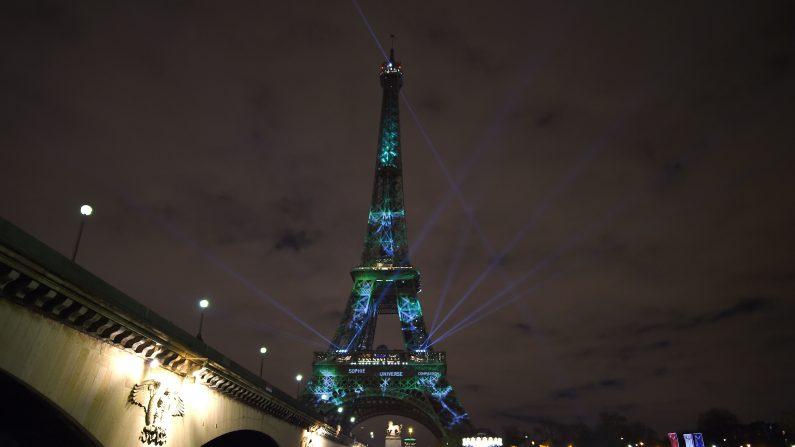 Una imagen tomada en 30 de noviembre 2015 muestra la Torre Eiffel iluminada de color verde y mensajes a contra el calentamiento global durante el primer día de la conferencia sobre el clima de las Naciones Unidas en París. El vigésimo primer período de sesiones de la Conferencia de las Partes (COP 21) de la Convención Marco de Naciones Unidas sobre el Cambio Climático tendrá lugar del 30 de noviembre al 11 de diciembre (Photo credit should read STEPHANE DE SAKUTIN / AFP / Getty Images)
