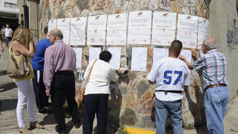 Los ciudadanos buscan sus nombres en la lista en un colegio electoral en Caracas, a 06 de diciembre 2015 durante las elecciones legislativas de Venezuela (Photo credit should read FEDERICO PARRA / AFP / Getty Images)