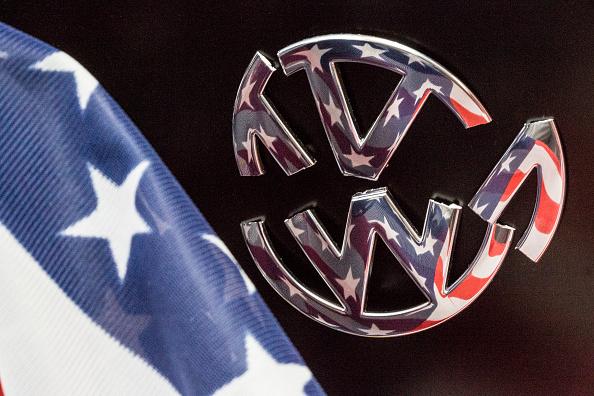Volkswagen y sus escándalos. La bandera de los Estados Unidos de América se refleja en un símbolo de Volkswagen en forma quebrada, por la demanda de la EPA. (Foto por Ulrich Baumgarten via Getty Images)
