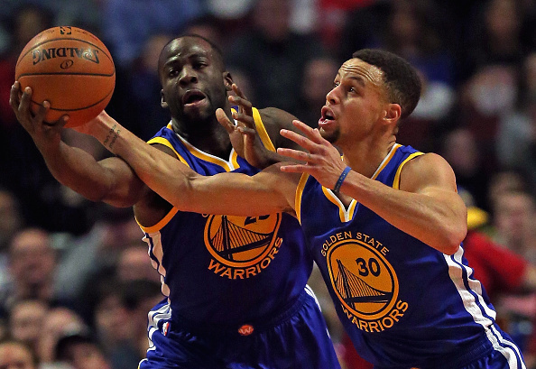 Draymond Green #23 (L) y los Golden State Warriors Stephen Curry #30 van para un rebote contra los Chicago Bulls en el United Center en 20 de enero de 2016 en Chicago, Illinois. (Foto por Jonathan Daniel/Getty Images)