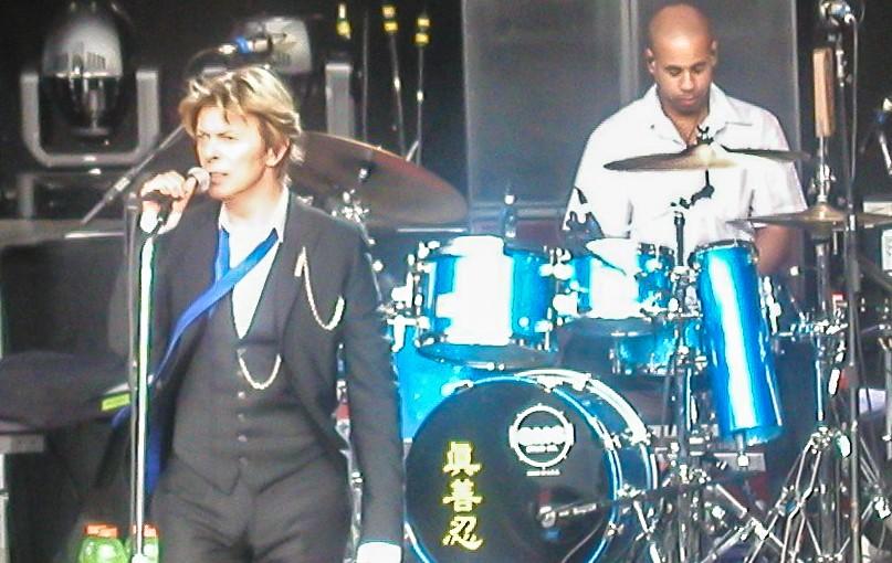 """David Bowie y Sterling Campbell tocan en San Francisco en 2002. Los tres caracteres chinos en la batería de Sterling significan """"Verdad, Benevolencia, Tolerancia"""", los tres principios guía de Falun Dafa, una disciplina espiritual de la Escuela Buda que Sterling practica."""