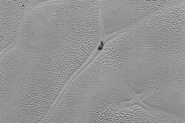 """Imagen enviada a la Tierra el pasado 24 de Diciembre por New Horizons donde se aprecia una intrigante forma de """"X"""" en Plutón. Image Credit: NASA/JHUAPL/SwRI"""