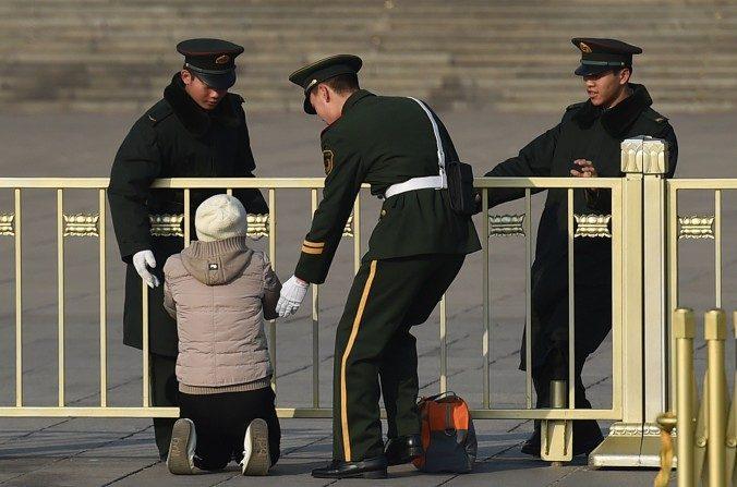 Policías paramilitares detienen a una mujer mientras protesta de rodillas frente al Gran Palacio del Pueblo en Beijing el 13 de marzo del 2015. (GREG BAKER / AFP / Getty Images)