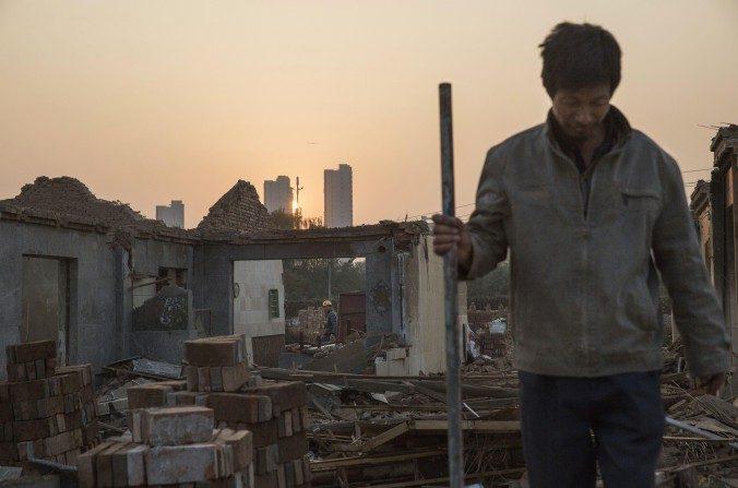 Trabajadores chinos demuelen una casa el 16 de octubre del 2015, del pueblo Gucheng, en el distrito de Tongzhou en Beijing. La oficinas municipales de Beijing se trasladarán desde el centro de la ciudad a las zonas periféricas como parte de un ambicioso proyecto de gobierno para crear una megaciudad urbana en el norte de China (Kevin Frayer / Getty Images)