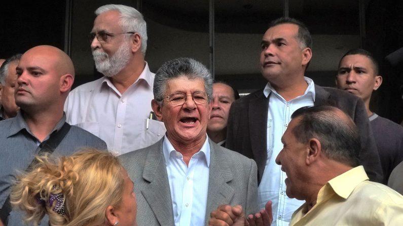 El nuevo presidente de la Asamblea Nacional, el diputado Henry Ramos Allup (C) se para frente a la Asamblea Nacional después de que se le negó a entrar en su nueva oficina en Caracas, el 4 de enero de 2016. Una tensa lucha por el control de la legislatura de Venezuela amenaza con llegado a un punto en una ceremonia de toma de posesión el martes como legisladores de la oposición desafían los esfuerzos del gobierno para debilitar su mayoría (Photo credit should read JUAN BARRETO / AFP / Getty Images)