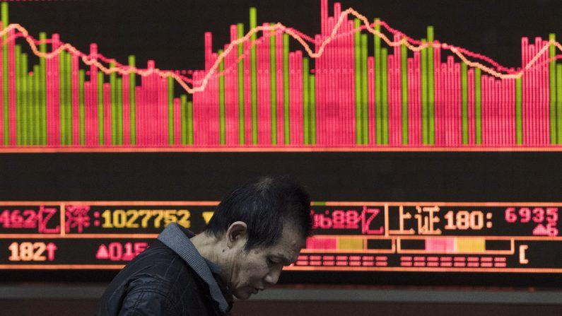"""Un inversionista camina delante de una pantalla que muestra los movimientos del mercado de valores en Beijing el 13 de enero de 2016. La desaceleración de China es una causa de """"riesgo"""" para las economías emergentes. (FRED DUFOUR/AFP/Getty Images)"""