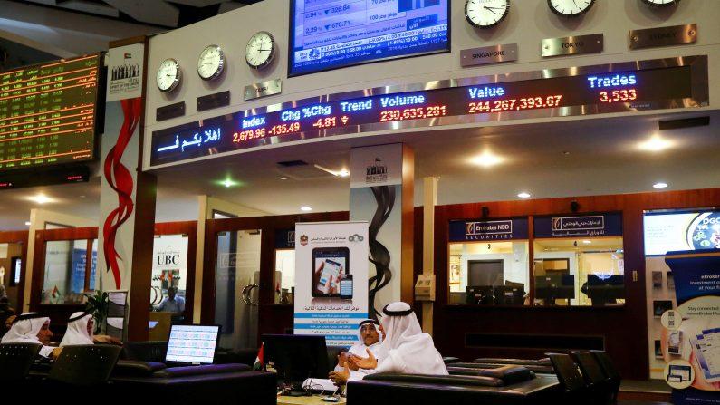 Proveedores en la bolsa de Dubai, precios de las acciones se reflejan en las pantallas en rojo el 17 de enero de 2016. Irán aumenta producción de petróleo y condena nuevas sanciones. (MARWAN NAAMANI/AFP/Getty Images)