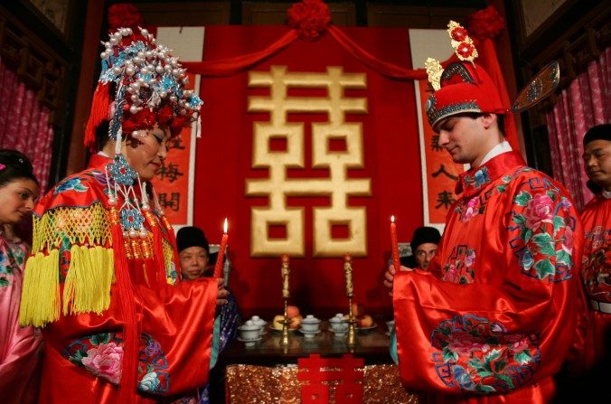 Una pareja de recién casados, el novio de Francia y la novia de China, asisten a su ceremonia de boda de estilo chino en el Gran Sight Garden, el 5 de mayo del 2007 en Beijing, China. (China Photos /Getty Images)