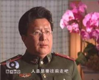 """El Dr. Shen Zhongyang en una entrevista con la televisión china, vestido con uniforme paramilitar. El subtítulo dice """"la humanidad siempre progresará""""."""