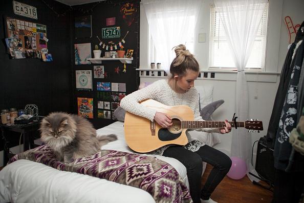 Tiffany Martin, 14, toca la guitarra en su habitación en su casa de la familia en un día de escuela en Madison, New Hampshire. Ella aprendió a tocar viendo videos en YouTube. (Foto por Melanie Stetson Freeman/The Christian Science Monitor via Getty Images)