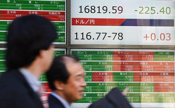Los empresarios junto a un tablero eléctrico cita intermitente el índice clave Nikkei de la bolsa de valores de Tokio (TSE) frente a una empresa de valores en Tokio en 05 de febrero de 2016. Acciones de Toshiba han buceado a una baja de más de 36 años después de la firma de escándalo-golpe amplió su pérdida anual prevé un friolera USD 6 billones, mientras que un yen fuerte arrastró los Nikkei en el rojo. (crédito de foto debe leer TORU YAMANAKA/AFP/Getty Images)
