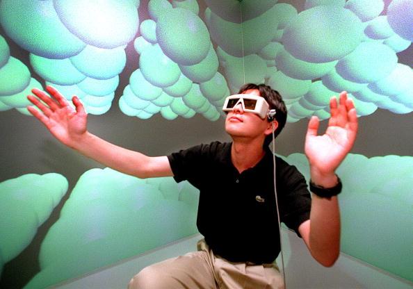 Un investigador del laboratorio de modelado inteligente de la Universidad de Tokio con unas gafas 3D, extiende su mano para tocar cómo se siente en el mundo microscópico en la sala de realidad virtual de un laboratorio. (Foto: YOSHIKAZU TSUNO/AFP/Getty Images)