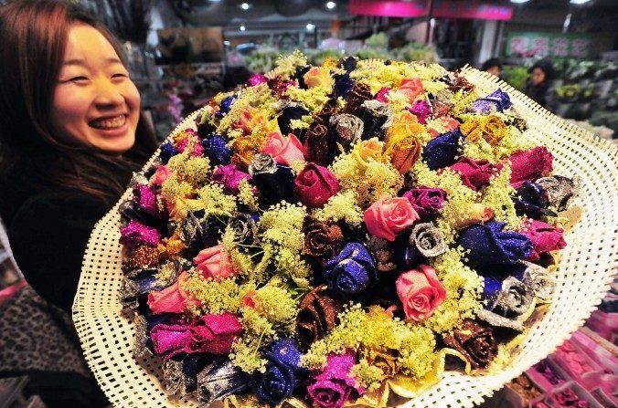 Una mujer posa con un ramo de rosas en un mercado de flores en China para el Día de San Valentín en esta foto de archivo. (ChinaFotoPress / Getty Images)