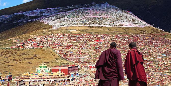 Monjes tibetanos budistas observan la ciudad del Tibet desde lo alto. (PAUL J. RICHARDS/AFP/Getty Images)