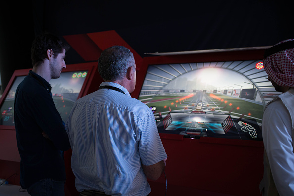 Los visitantes juegan con realidad virtual que simula carreras un zumbido a lo largo de la pista diseñada para finales en el drone mundo zángano Prix Campeonato en Dubai, Emiratos Árabes Unidos, que compitió desde el viernes, 11 de marzo de 2016. Los equipos compiten para el bolso campeón mundial de premios total de $ 1 millón por navegando por drones en sobre 100 km hora por una pista que cuenta con múltiples vías, obstáculos estáticos y cinéticos diseñado para pilotos a sus límites. Fotógrafo: Razan Alzayani/Bloomberg a través de Getty Images