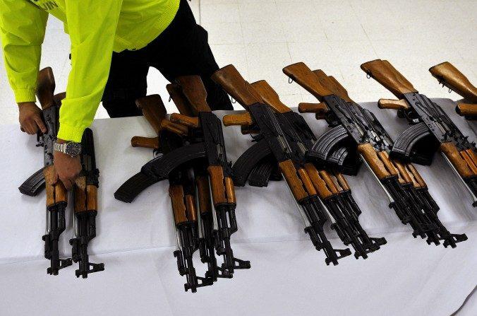 Un oficial de policía de Colombia organiza rifles de asalto incautados en Cali, departamento del Valle del Cauca, Colombia, el 29 de julio de 2011. La policía colombiana incautó 47 fusiles Norinco de asalto, calibre 7,62 mm de fabricación china (réplicas del AK-47) y 214 revistas. (Luis Robayo / AFP / Getty Images)