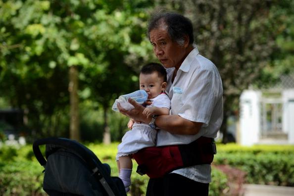 Un adulto mayor alimenta un bebé en una zona residencial de Beijing, el 08 de agosto de 2013. (WANG ZHAO/AFP/Getty Images)